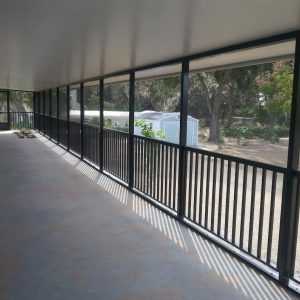 Black fence lining a long screen enclosure - Carport on one side and a long screen enclosure on the other