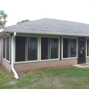 Four replacement windows with dark frames and dark door