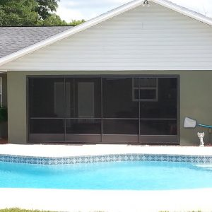 Poolside sliding garage screen door for patio enclosure