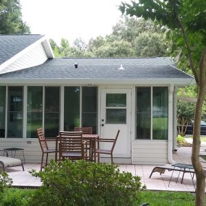 Outside view of the backdoor - White sunroom with tall windows