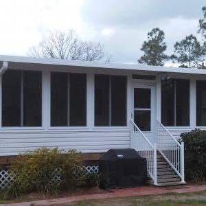 Outside overview of the backdoor - White siding, wooden deck foundation sunroom
